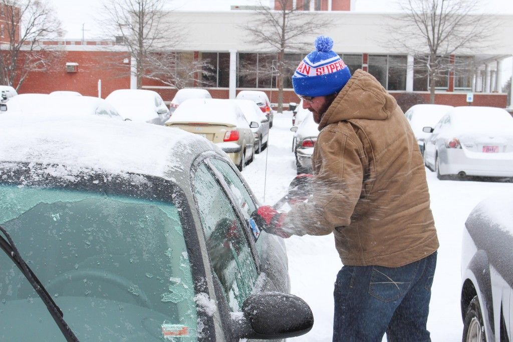 Thomas Whited, graduate student from Kansas City, Mo., removes ice and snow from his car during February's snowstorm.