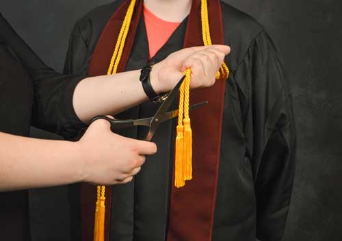 Photo Illustration by Hannah Fowl/The News Gold cords are given to students who achieve honors such as cum laude with their graduation robes.