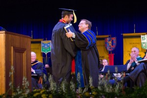 President Bob Davies embraces Michael Dobbs, student regent, after his speech Friday. Fumi Nakamura/The News