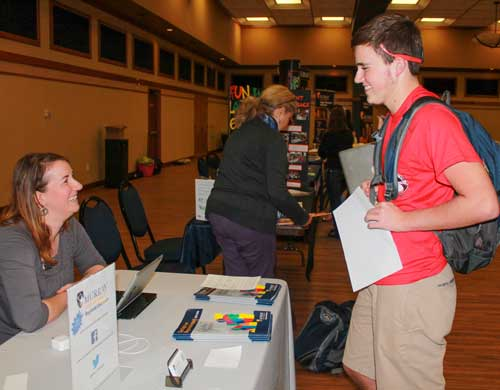 Jenny Rohl/The News Sophomore Sawyer Rambo visits the Regional Outreach table at the Real World Market.