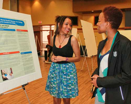 Jenny Rohl/The News Egypt Crider, senior from Metropolis, Ill., presents the results of her research to Chesika Crump, senior from Hopkinsville, Ky.