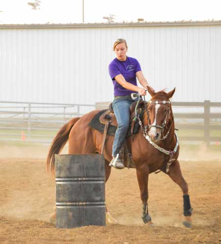 Emily Harris/The News Ellen Adams from McDonough, Georgia practices barrel racing for an upcoming college rodeo in Marshall, Missouri.
