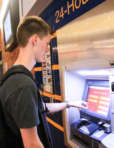Jenny Rohl/The News Kristian Hoybye, freshman from Denmark, uses an ATM in the Curris Center.