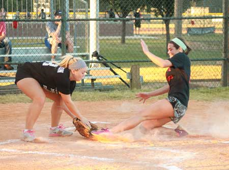Jenny Rohl/The News Freshman Jordyn Thornell slides into home as junior Emily McFerron catches the ball on base.