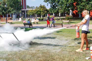 McKenna Dosier /The News Leah Krause, graduate student from St. Charles, Missouri, learned how to properly use a fire extinguisher during Campus Fire Safety Day Thursday afternoon.
