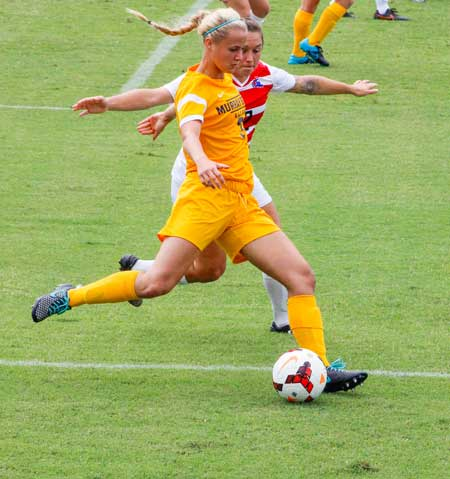 McKenna Dosier/The News Caroline Ashton, freshman forward and midfielder attempts to kick the ball past mid field during the Racers Sept. 11 game against Louisiana Tech.