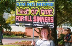 Jenny Rohl/The News Leah Hoeck, one of the younger members of the church, held the provocative signs as her family members stood beside and explained their views.