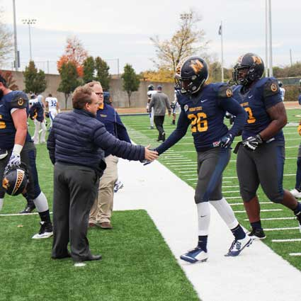 Nicole Ely/The News President Bob Davies shakes the hand of sophomore running back Demetric Johnson as he runs off the field after the game against Eastern Illinois Saturday.