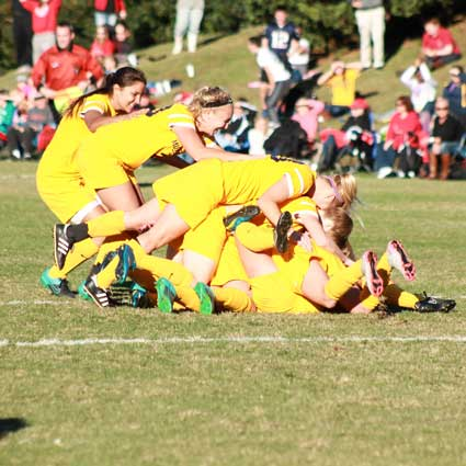 Jenny Rohl/The News The Racers pile up in celebration after scoring the game-winning goal in overtime to earn their second OVC Tournament title.