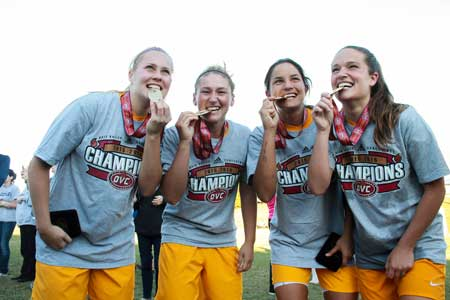 Jenny Rohl/The News Rebecca Bjorkvall, senior midfielder, Racheal Foxley, senior defender, Nyomi Devine, sophomore defender and Taylor Stevens, senior midfielder, celebrate soccer's championship win on Nov. 8.