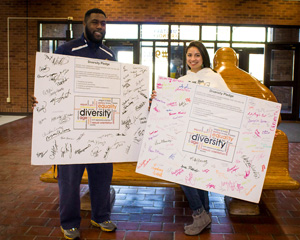 Savana Smothers/The News Two students hold the Diversity Pledge boards in the Curris Center. The pledge has received half of the 5,000 signature goal.