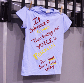 Emily Harris/The News Hannah Barney, left, speaks about how it can be difficult for sexual assault survivors to speak up. Shirts, like the one on the right, were displayed around the CFSB Center, encouraged students to find their voice and tell their stories.