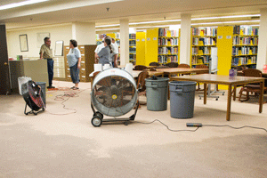 Nahiomy Gallardo/The News Waterfield Library staff clean up water after pipes overflow in the basement.