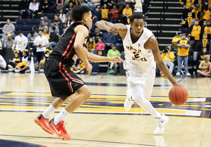 Nicole Ely/The News Moss dribbles past defender during his senior year, in which he contributed 14.2 points per game. He helped lead the Racers to get their 29th consecutive winning season.